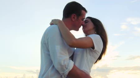 медовый месяц : Honeymoon passionate couple kissing at sunset. romantic in love kissing at beach sunset. Newlywed happy young couple enjoying ocean sunset during travel holidays vacation getaway.