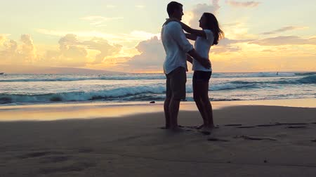 медовый месяц : Honeymoon playful young couple. Woman jumping man lifts her up. romantic in love kissing at beach sunset. Newlywed happy young couple enjoying ocean sunset during travel holidays vacation getaway.