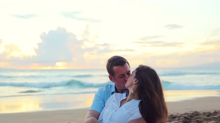 in : Honeymoon passionate couple holding each other sitting on beach. romantic in love kissing at beach sunset. Newlywed happy young couple enjoying ocean sunset during travel holidays vacation getaway. Shallow Depth of Field  Stock Footage