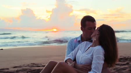 miłość : Attractive Young Brunette couple holding each other. romantic in love kissing at beach sunset. Newlywed happy young couple enjoying ocean sunset during travel holidays vacation getaway. Wideo