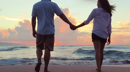 медовый месяц : Honeymoon passionate couple holding hands walking down the beach. Beautiful Sun Flares. Romantic Newlywed happy young couple enjoying ocean sunset during travel holidays vacation getaway freedom joy.  Shot with Steadicam.