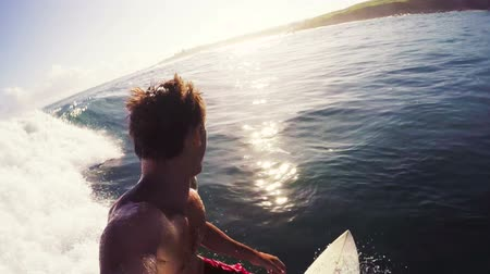 surfovat : Surfer Riding into Sunrise. Point of View Looking Over Shoulder Down the Line. Big Blue Ocean Surf in Hawaii. Dostupné videozáznamy
