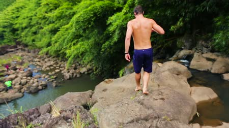 cliff : Young Fit Men Diving Cliff Jumping off Bamboo Forest Waterfall in Hawaii.