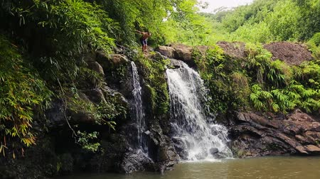 alpes : Young Fit Men Diving Cliff Jumping off Bamboo Forest Waterfall in Hawaii.