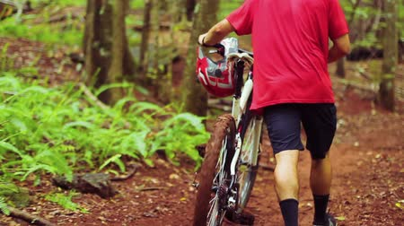 serbest : Young Man Walking Mountain Bike Uphill on Forest Trail.  Outdoor Sports Healthy Lifestyle. Slow Follow Shot with Steadicam. Summer Extreme Sports.