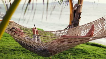 hawaii : Revealing Pan of Beautiful Blonde Young Woman with Curly Hair Using Mobile Smart Phone while Relaxing in a Hammock by the Ocean Between Palm Trees at Sunset in Hawaii.