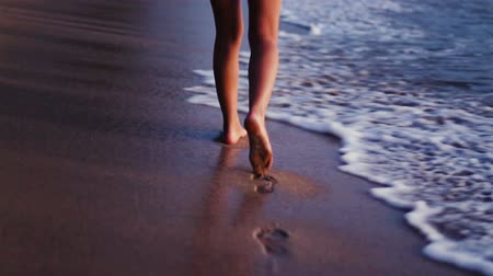 sunset sea : Legs only young ethnic girl walking barefoot along wet sand beach waves gently rolling Sunset Evening Romantic Color Tone.