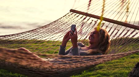 гамак : Young Woman Texting and Reading on Smart Phone in Hammock. Sunset Warm Red Color Tone. Beautiful Curly Blonde Hair. Swinging Hammock Between Palm Trees