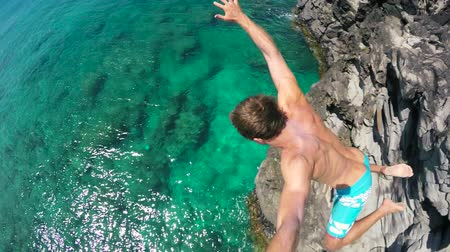 kayalık : Slow Motion POV Young Man Jumping from cliff into the ocean in Hawaii. Summer fun lifestyle. Beautiful Blue Ocean Sunny Day. SLOW MOTION Stok Video