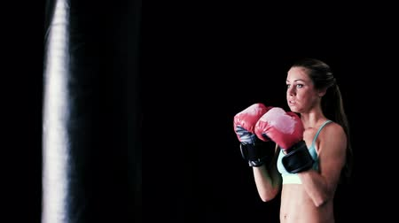 bolsa : Strong Female Athlete Exercising for Self Defense with Boxing Gloves and Body Bag. Athletic Woman Fitness Training in Gym. Dramatic Lighting and Tough Tone.