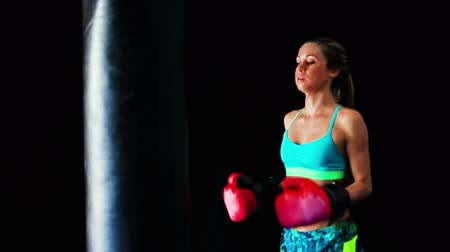 bokszoló : Beautiful Young Female Athlete Exercising for Self Defense with Boxing Gloves and Body Bag. Athletic Woman Fitness Training in Gym. Dramatic Lighting and Tough Tone.