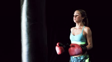 подготовке : Beautiful Young Female Athlete Exercising for Self Defense with Boxing Gloves and Body Bag. Athletic Woman Fitness Training in Gym. Dramatic Lighting and Tough Tone.