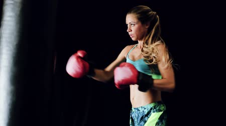powerful : Beautiful Strong Young Female Boxer Training with Red Gloves on Black Body Bag with Dramatic Contrast Lighting.  Stock Footage