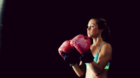boksör : Beautiful Young Female Athlete Exercising for Self Defense with Boxing Gloves and Body Bag. Athletic Woman Fitness Training in Gym. Dramatic Lighting and Tough Tone.