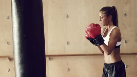 gyönyörű nő : Beautiful Young Female Athlete Exercising for Self Defense with Boxing Gloves and Body Bag in Gym. Athletic Woman Fitness Training in Gym.  Stock mozgókép