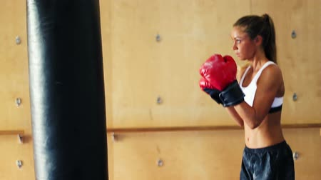 подготовке : Beautiful Young Female Athlete Exercising for Self Defense with Boxing Gloves and Body Bag in Gym. Athletic Woman Fitness Training in Gym. Dramatic Lighting and Tough Tone.
