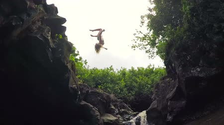 cliff : Slow Motion Young Woman in Bikini Back Flip Jumps off Cliff Into Water. Summer Fun Outdoor Lifestyle. Lush Green Jungle Waterfall Pond.