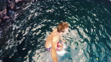 taş : Slow Motion POV Young Man Jumping from cliff into the ocean in Hawaii. Summer fun lifestyle. Beautiful Blue Ocean Big Sea Cave in Background. SLOW MOTION Stok Video
