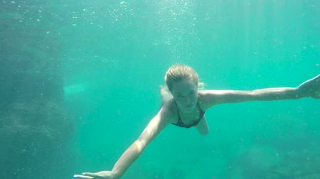 sualtı : Woman Swimming Underwater. Swimming Towards Camera by Coral Reef in Ocean in Hawaii. Young Attractive Beautiful Woman Mermaid. Stok Video