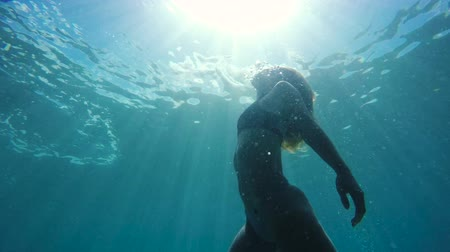 gyönyörű nő : Woman swimming underwater towards surface with beautiful sun flares in slow motion. Beautiful Attractive Female Mermaid.