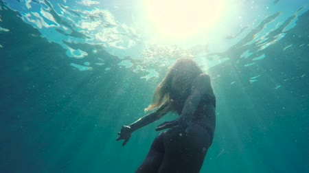 swimming underwater : Woman in Bikini swimming underwater towards surface with beautiful sun flares. Stock Footage