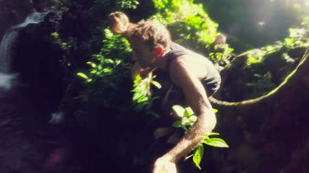 cliff : Young Cute Adventure Couple Holding Hands and Jumping off Cliff into Lush Jungle Waterfall Pond. Slow Motion  Stock Footage