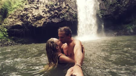 selfie girl : Cute Young Couple Holding Kissing in front of Waterfall with POV Selfie Stick. Happy cheerful young multicultural couple on travel. Lush Green Waterfall in Hawaii. Slow Motion