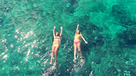 deitado : Aerial View of Beautiful young hawiian women floating with blonde girl friend swimming in bikinis