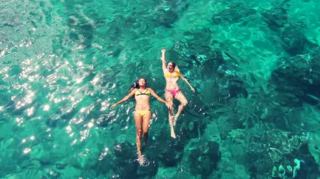 приморский : Aerial View of Beautiful young hawiian women floating with blonde girl friend swimming in bikinis