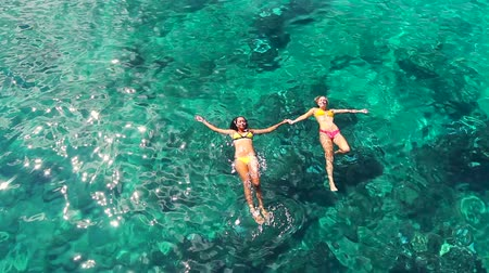 tyrkysový : Aerial View of Beautiful young women floating swimming in bikinis holding hands Dostupné videozáznamy