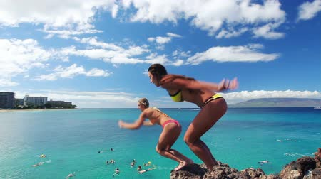 kayalık : Two Girl Friends Ethnic DIverse Jump Off Cliff into Ocean in Bikinis in Hawaii. Summer Outdoor Lifestyle. Stok Video