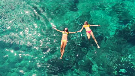 holiday villa : Aerial View of Beautiful young women relaxing floating swimming in bikinis