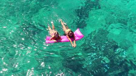 deitado : Beautiful Young Women In Bikinis Floating on Pink Inflatable Raft in Crystal Ocean in Hawaii. Summer Fun Vacation Lifestyle. Diverse Ethnic Pacific Islander Hawiian Girl with Blonde Girl Friend.