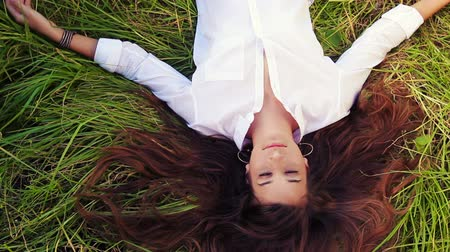 луг : Beautiful Girl Lying on the Meadow and Dreaming. Enjoy Nature. Beautiful Brunette. Eyes Closed.