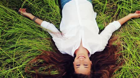 trawnik : Beautiful Girl Lying on the Meadow and Dreaming. Enjoy Nature. Beautiful Brunette Blinks Open Eyes and Smiles