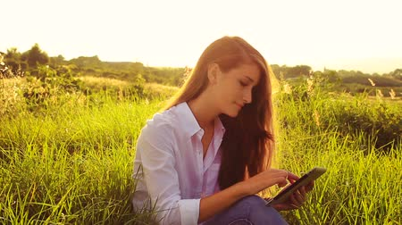 natura : Young Woman Using Tablet Computer Touchscreen Outside in Nature. Modern Technology Outdoors. Woman Sitting in Park in Green Grass. Wideo