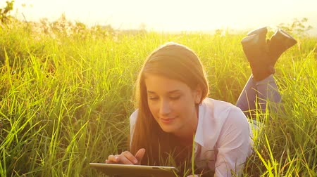 lifestyle : Young Woman Using Tablet Computer Touchscreen. Beautiful Sunset Light. Outdoor Healthy Lifestyle with Modern Technology.
