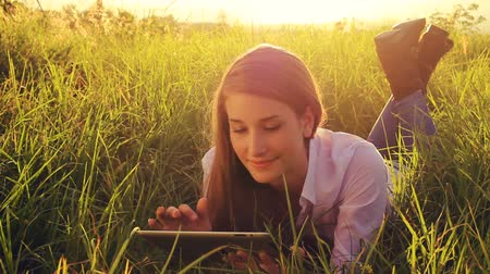 touchpad : Young Woman Using Tablet Computer Touchscreen. Outdoor Healthy Lifestyle with Modern Technology. Beautiful Sunset Light in Green Grassy Park. Stock Footage