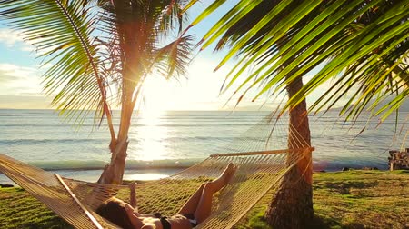 sunset sea : Beautiful Young Woman Relaxing in Tropical Hammock at Sunset. Bikini Summer Vacation. Stock Footage
