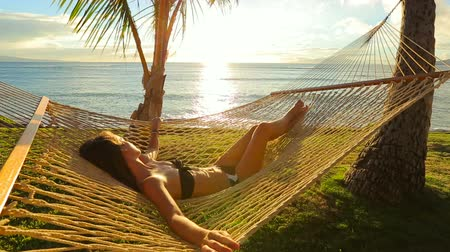 vacation destination : Beautiful Young Woman Relaxing in Tropical Hammock at Sunset. Bikini Summer Vacation. Stock Footage