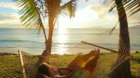 гамак : Romantic couple relaxing in tropical hammock at sunset Стоковые видеозаписи