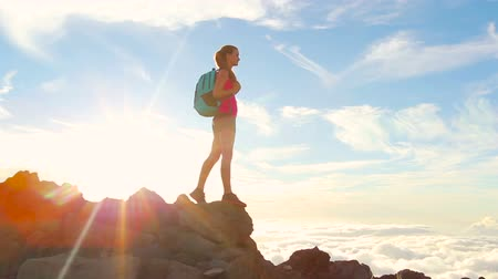 kaland : Hiker with Backpack Hiking on top of a mountain with sun flares. Young Woman Healthy Active Lifestyle. Adventure in Nature. Stock mozgókép