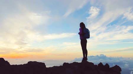 kaland : Reaching The Top. Lone female at sunset celebrates achieving her mountain hike above the clouds. Helathy Active Lifestyle. Adventure in nature. Stock mozgókép