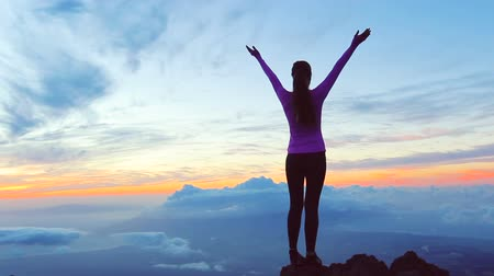 cíle : Reaching The Top. Happy successful fitness woman raising arms to the sky at sunset. Success Dostupné videozáznamy