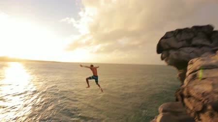 cliff : Young Man Jumps off Cliff Into Water. Summer Extreme Sports Outdoor Lifestyle. Cliff Jumping at Sunset.