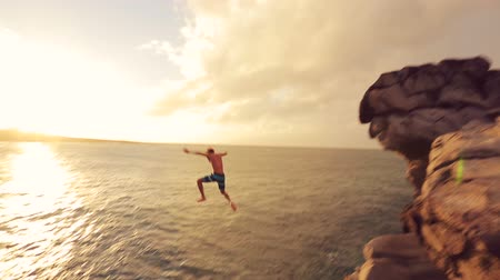 magasság : Young Man Jumps off Cliff Into Water. Summer Extreme Sports Outdoor Lifestyle. Cliff Jumping at Sunset.