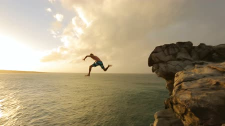 экстремальный : Young Man Jumps off Cliff Into Water. Summer Extreme Sports Outdoor Lifestyle. Cliff Jumping at Sunset.