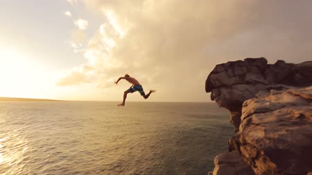 kayalık : Young Man Jumps off Cliff Into Water. Summer Extreme Sports Outdoor Lifestyle. Cliff Jumping at Sunset.