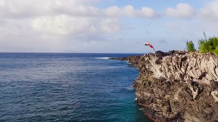 évad : Extreme Cliff Jumping Backflip. Summer Extreme Sports Shot from Above Aerial View. Cliff Jumping into Blue Ocean.