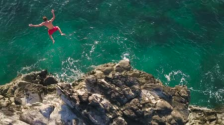 magasság : Cliff Jumping into Ocean. Aerial View Slow Motion. Young Man Jumps off Cliff Into Blue Ocean. Summer Extreme Sports Outdoor Lifestyle. Stock mozgókép